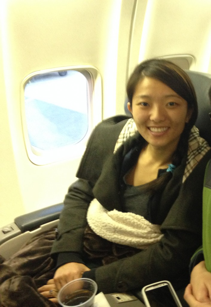 girl sitting in first class seat on plane with blanket wrapped around legs