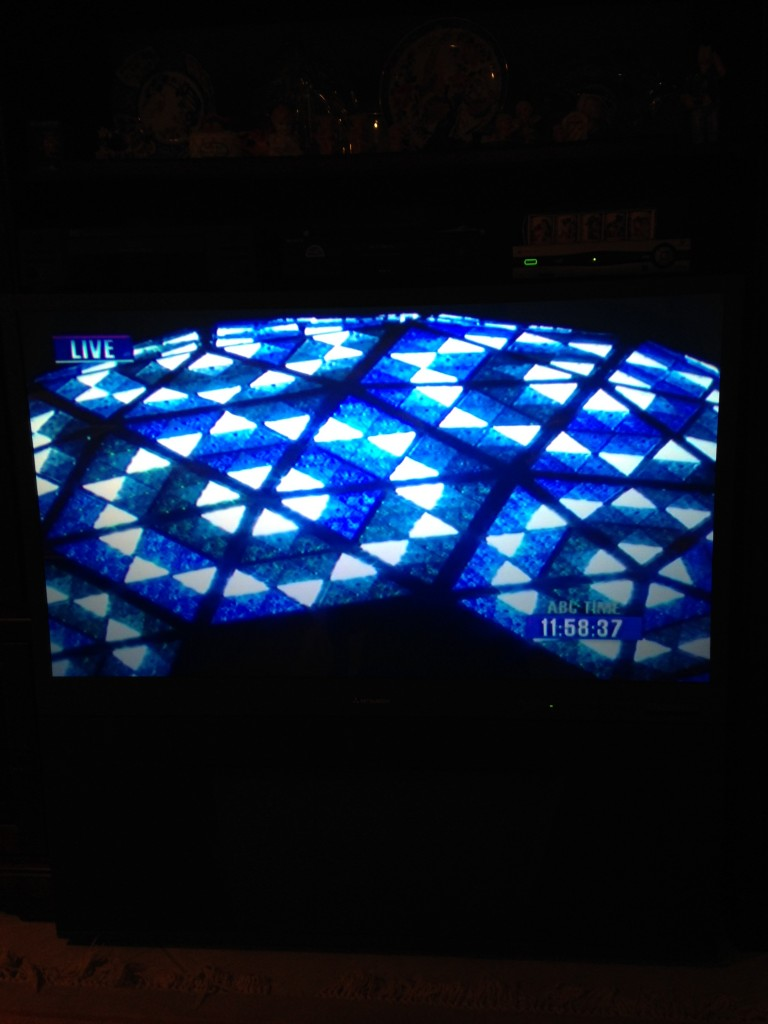 zoomed in view of times square new years ball lit up in blue on tv for new years eve celebration in nyc