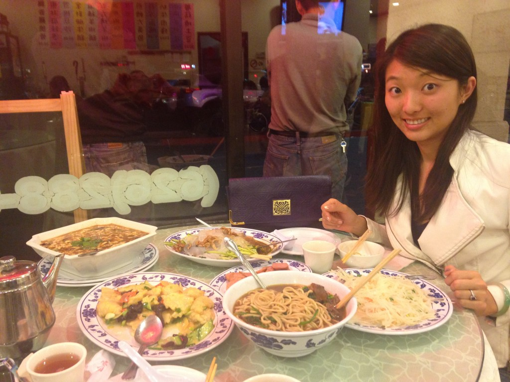 table filled with giant dishes of northern chinese food and girl looking skeptical about two people eating it all
