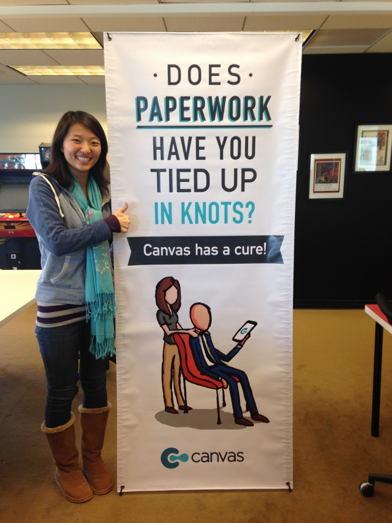 "girl holding thumbs up standing next to canvas vertical banner with ""does paperwork have you tied up in knots? canvas has a cure!"" messaging"