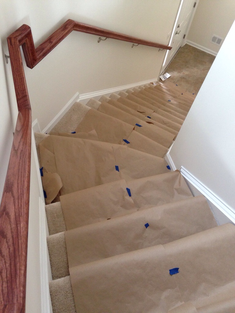 carpeted stairs covered in brown paper taped together with blue painter's tape