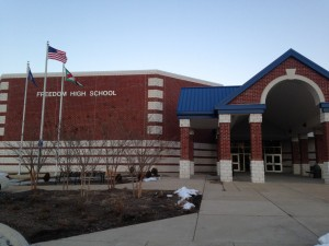 front of freedom high school with entrance, school name, and flags flying