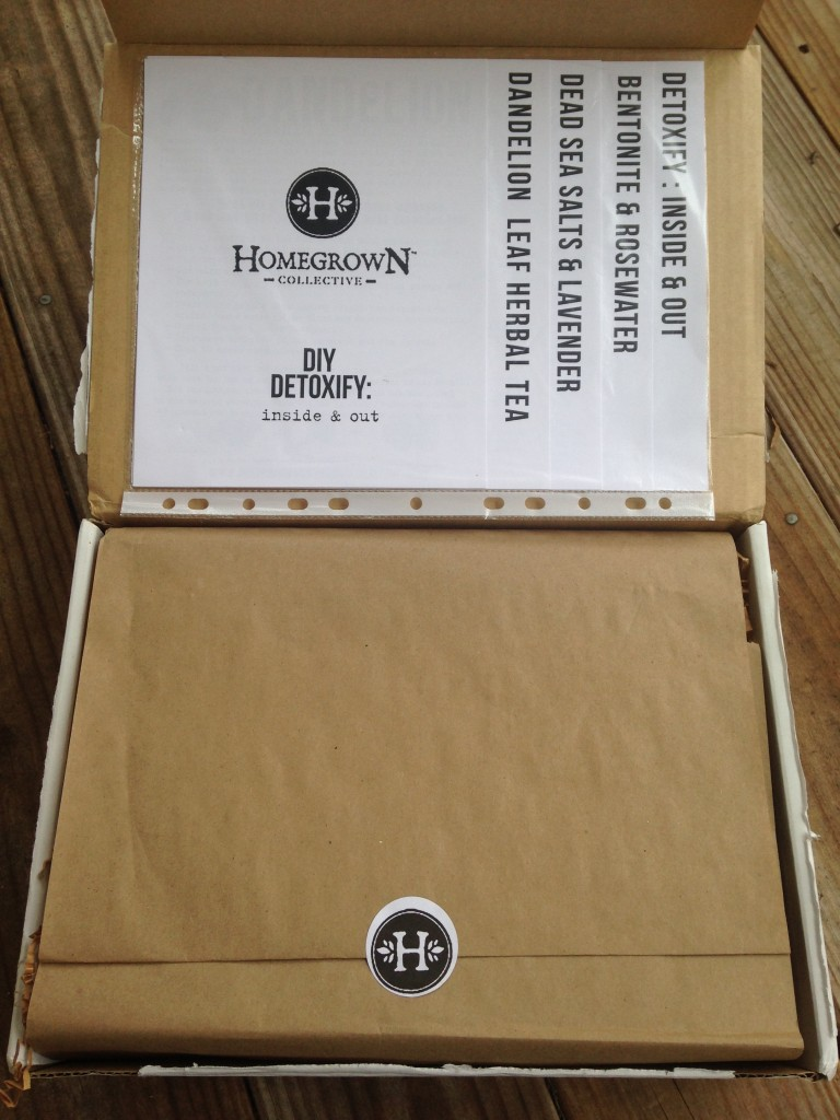 inside of homegrown collective box with the info sheets on the inner lid and white homegrown collective sticker on brown paper wrapping