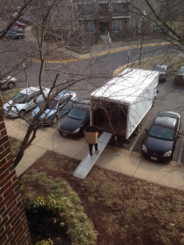 view of moving truck and guy going up ramp with boxes from third story apartment