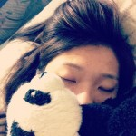 girl sleeping with toy panda covering part of face
