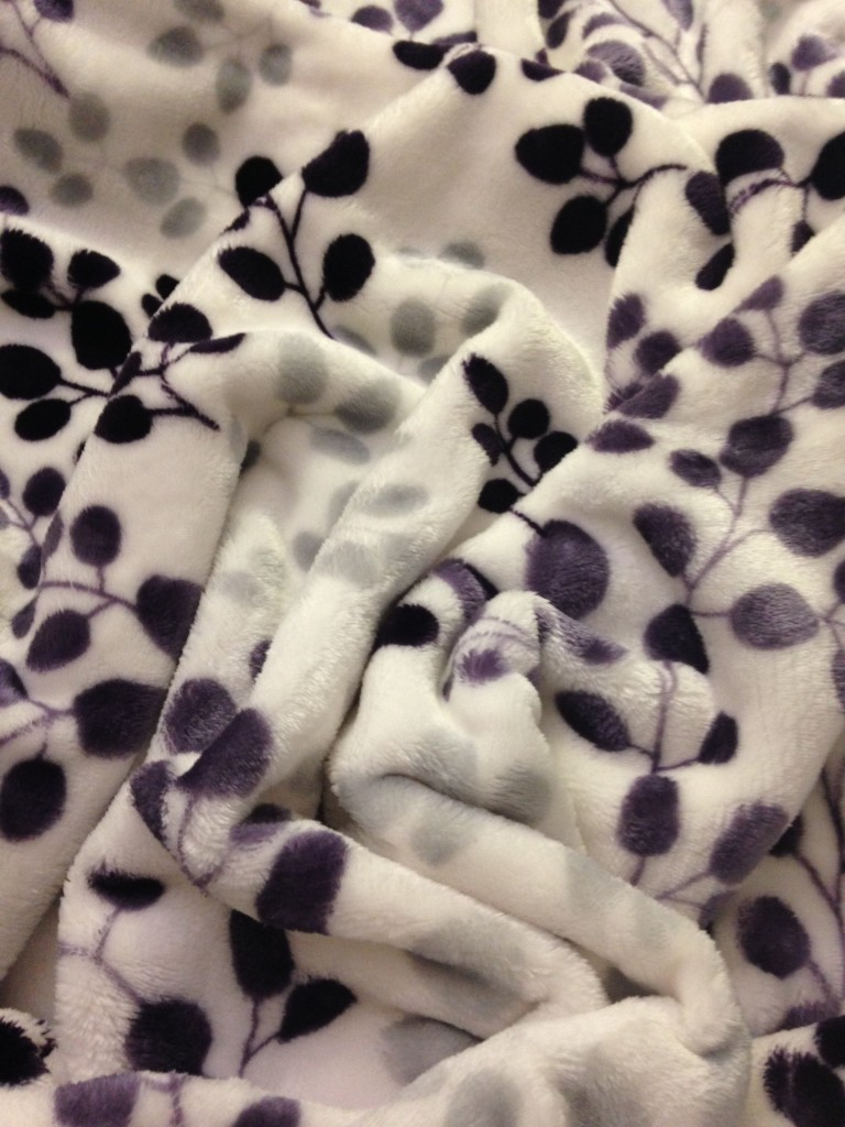 white plush blanket with purple and gray leaf pattern