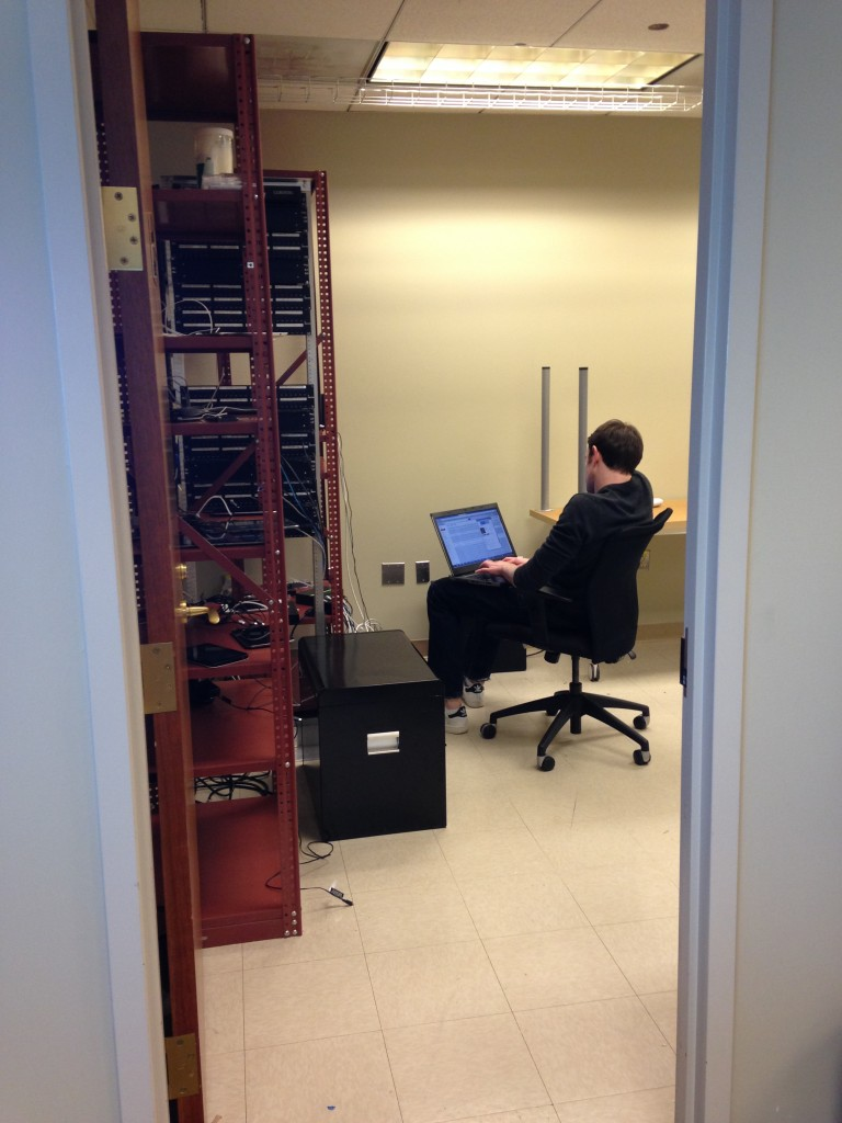 guy sitting in server room working on laptop