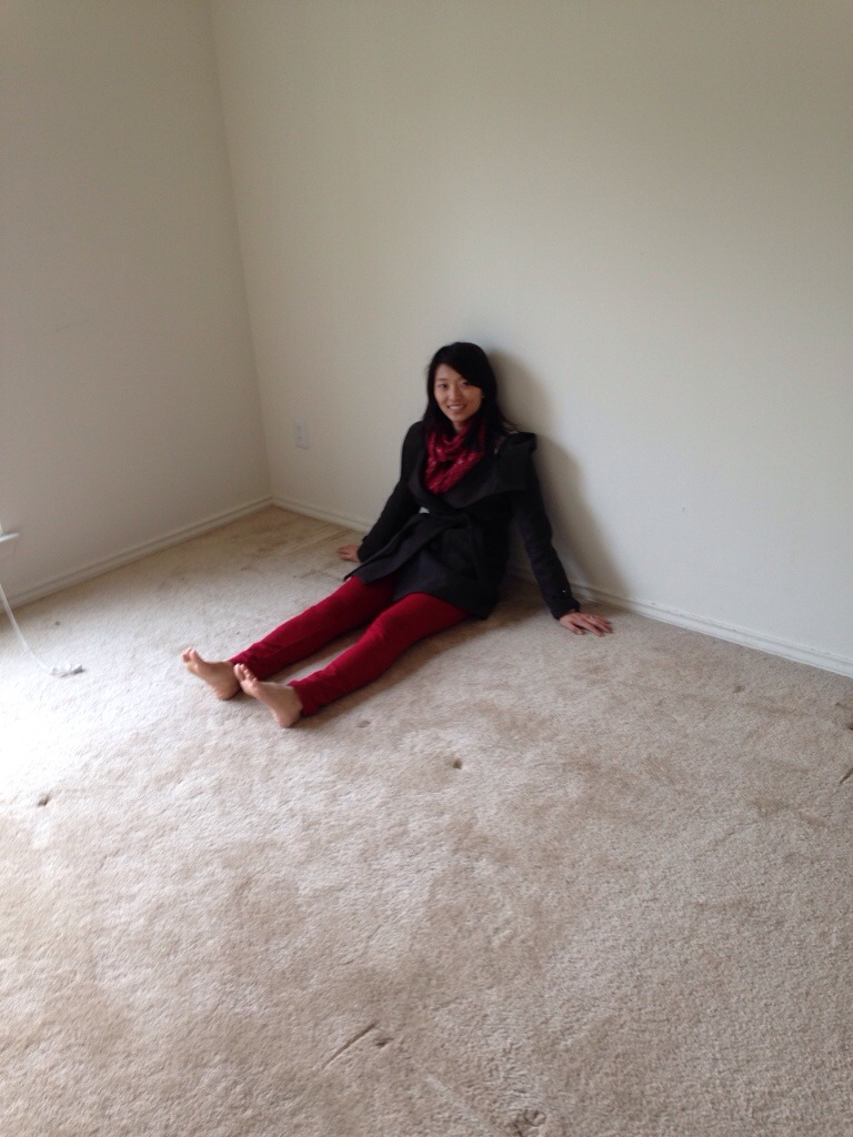 girl sitting against wall of empty room