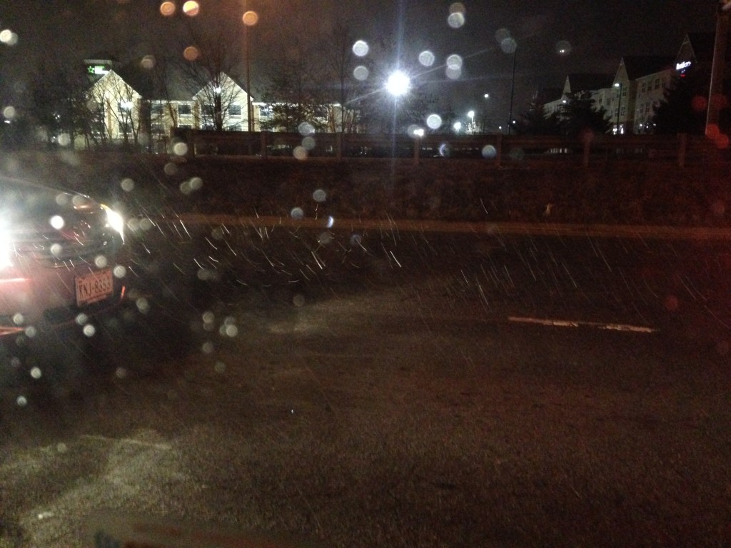 beginning of snow storm with flakes falling on road