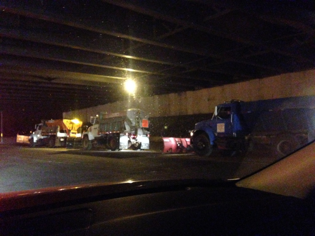 snow plows idling under overpass waiting for snow