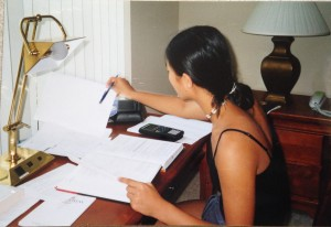 girl sitting at hotel desk studying with textbook, homework, and graphing calculator