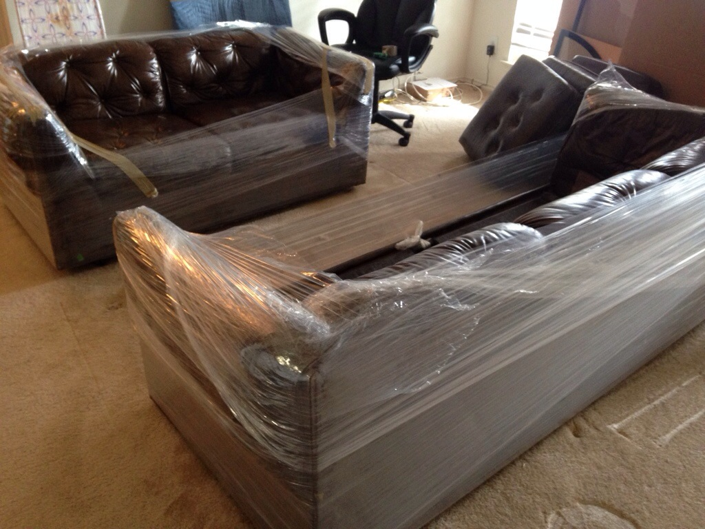 leather couches wrapped in plastic wrap
