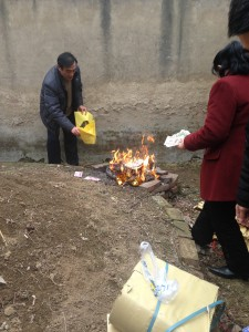 paying respects burning chinese paper money at ancestor's dirt mound grave site
