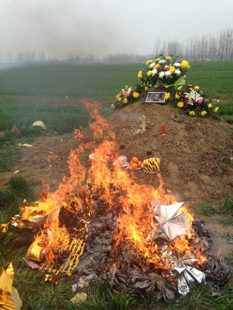 giant pile of paper money burning in front of dirt mound grave site