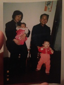 grandmother holding granddaughter and grandfather holding on to grandson
