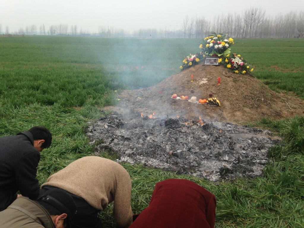 kow towing at grave site with smouldering ashes of burning paper