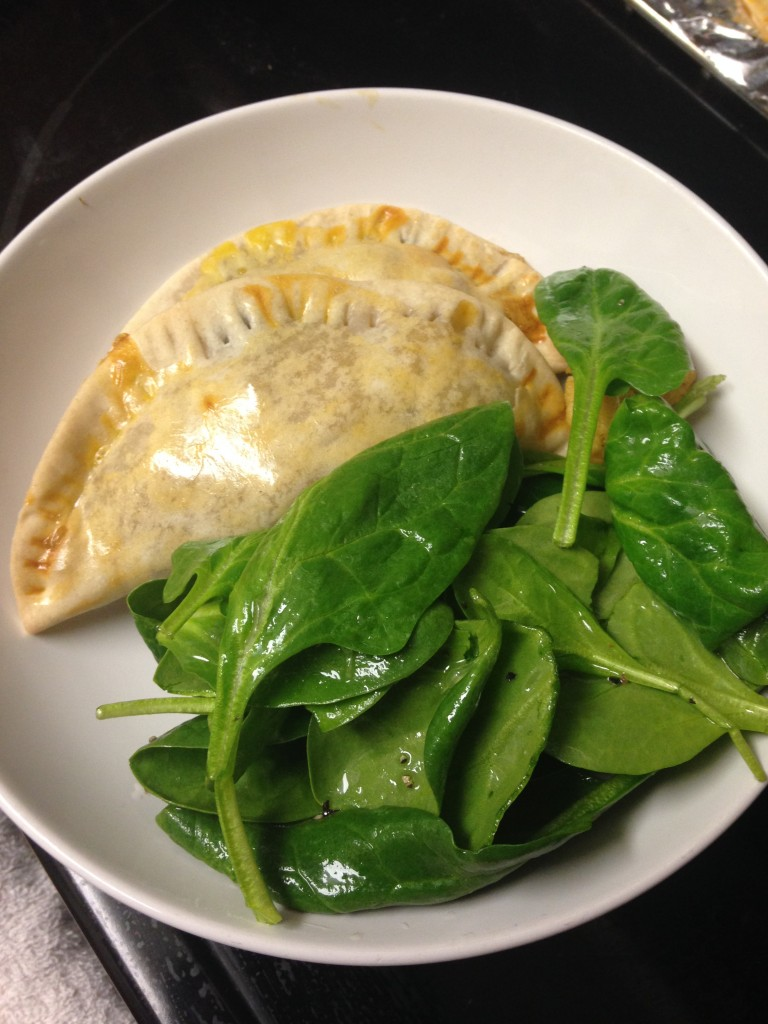 plate of spinach and cauliflower empanadas with spinach salad