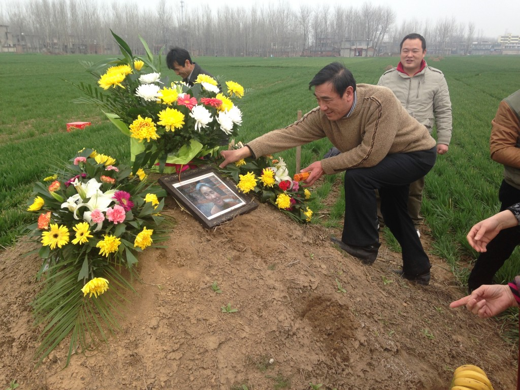 setting up dirt mound grave with flowers, picture, and offerings