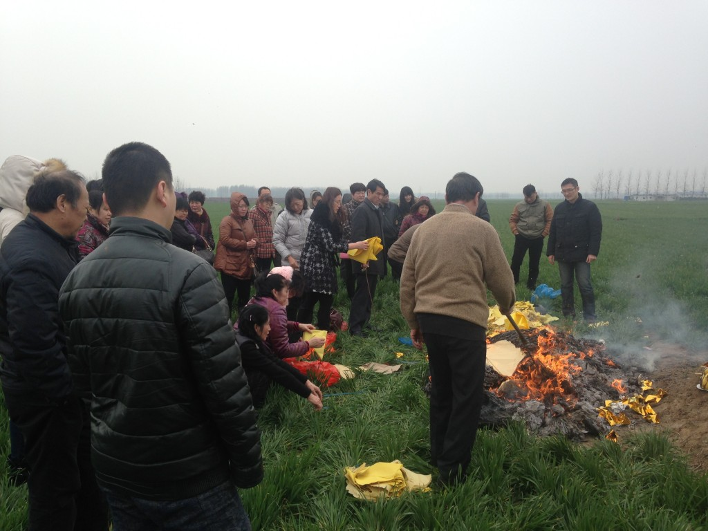 stoking large pile of burning paper at grave site