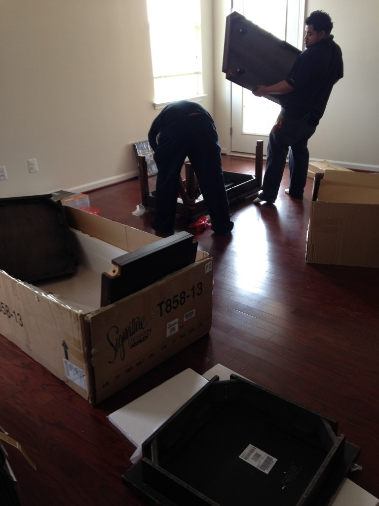 boxes of end tables and coffeetable with two guys assembling the pieces