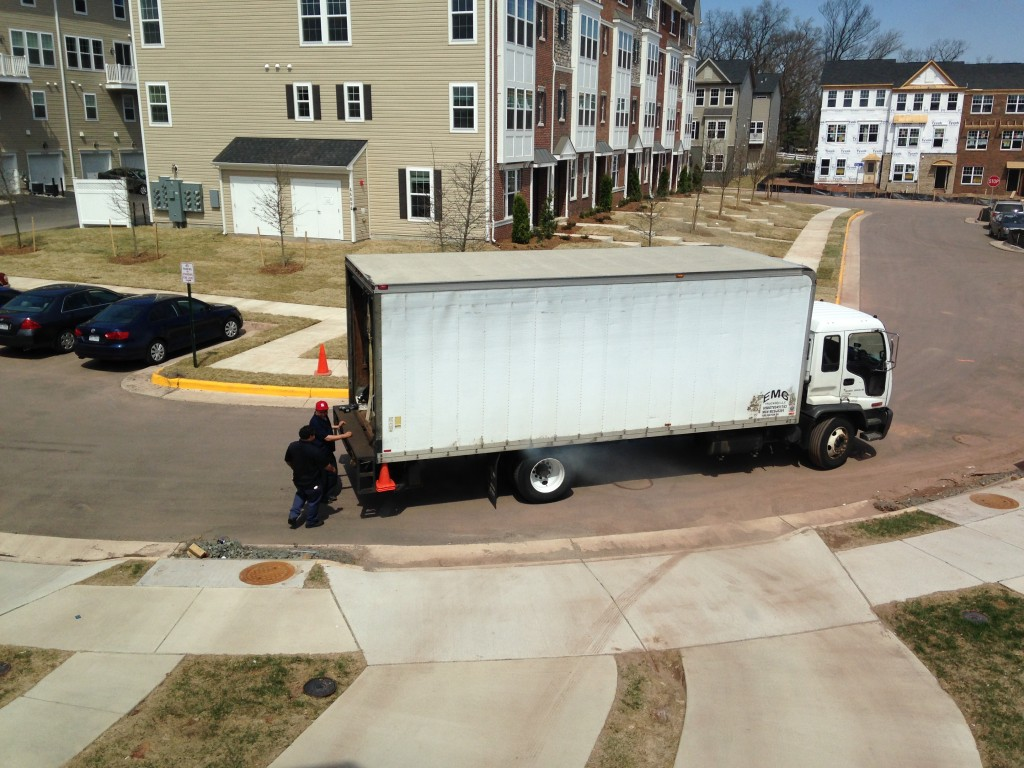 large white truck filled with furniture stopping for couch delivery