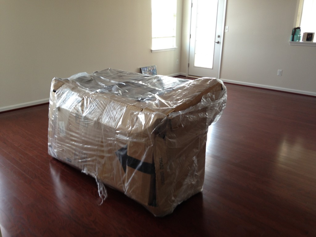 couch wrapped up in cardboard and plastic