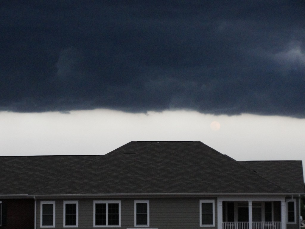 moon shining in distance as storm clouds creep across sky