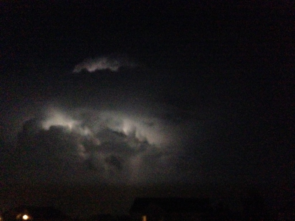 lightning behind cloud at night, lighting up parts of cloud in the darkness