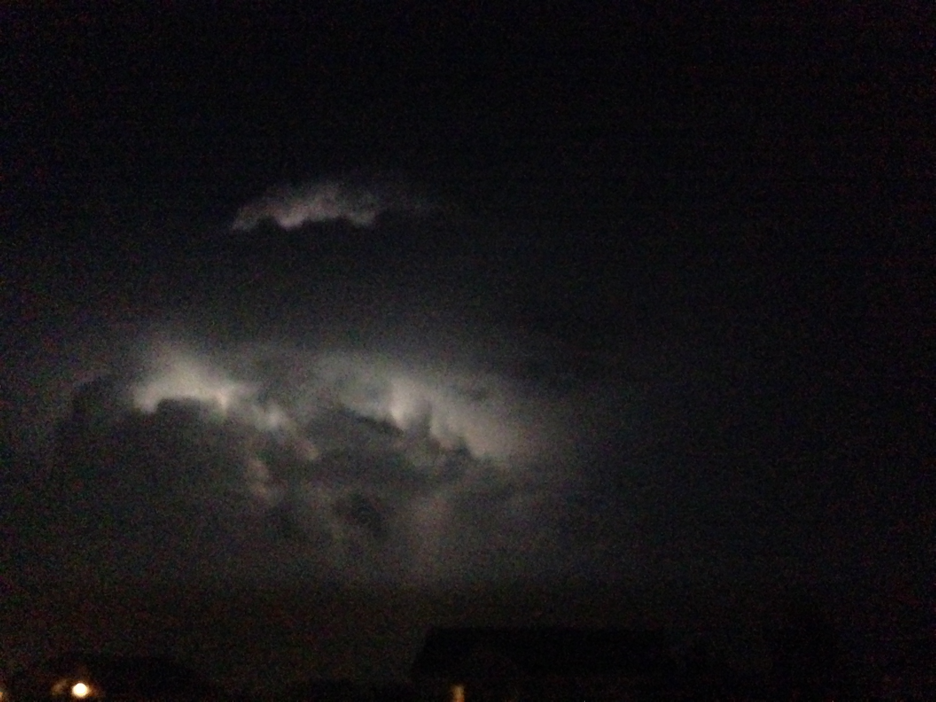 Lightning Behind Cloud At Night Lighting Up Parts Of In The Darkness