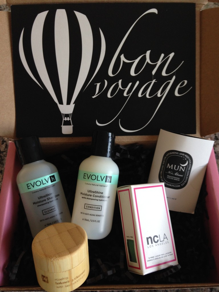 contents of petit vour june 2014 box with evolvh shampoo and conditioner, tay balancing cleanser, mun brightening serum, ncla luxury nail lacquer, and info card with bon voyage theme