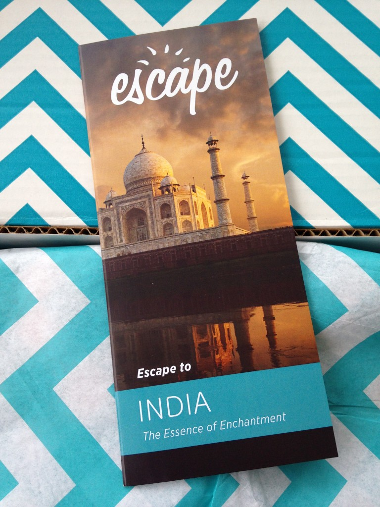escape monthly july india box info card against blue and white chevron background