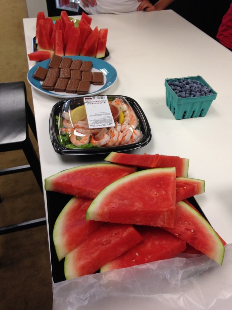 watermelon, blueberries, cocktail shrimp, and tim tams spread out on table for office happy hour