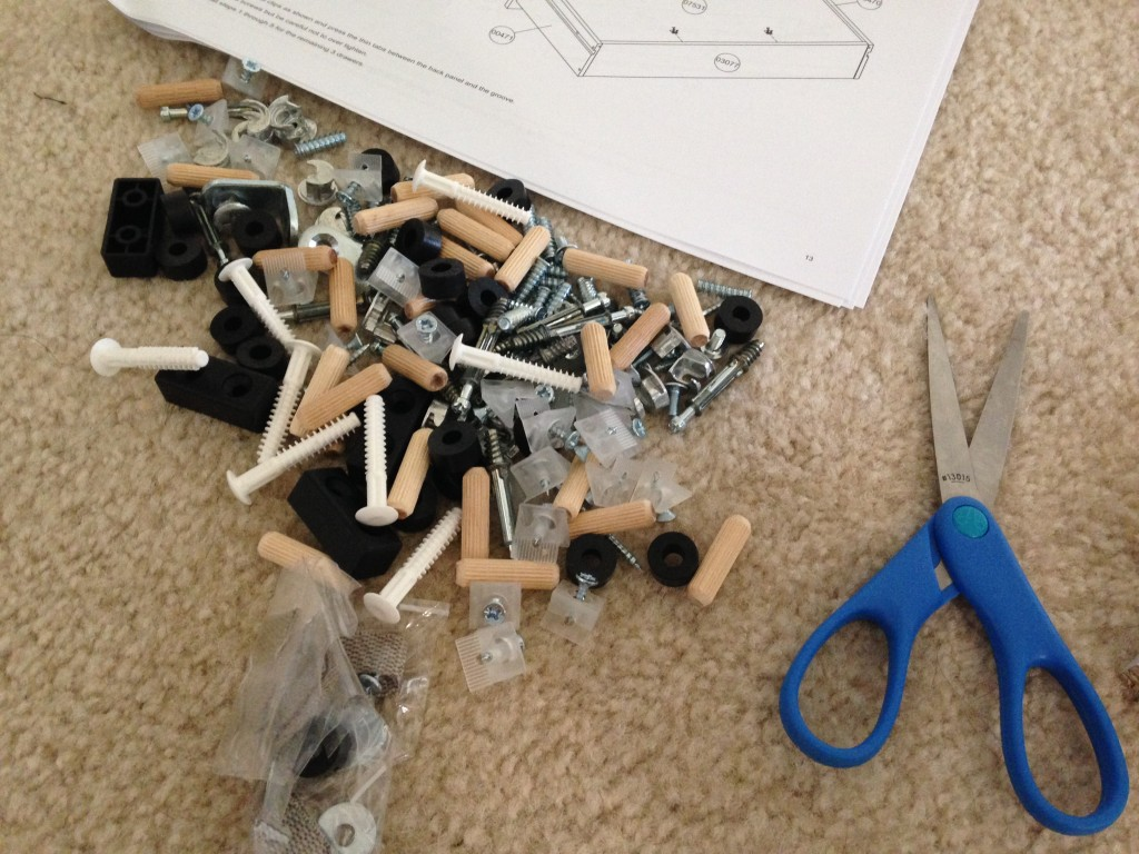 pile of screws, dowels, cams, and other hardware for dresser