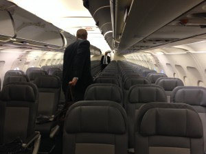 rows of empty seats on plane as first people start boarding and flight attendant waits near back