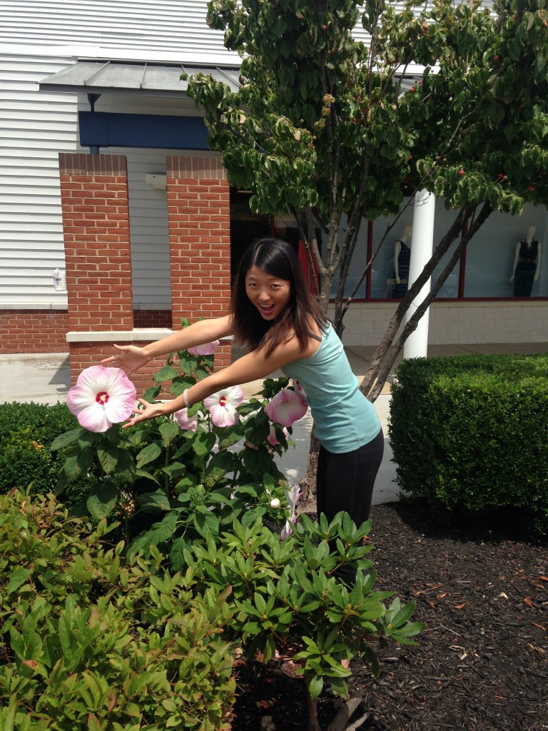 girl stretching hands out towards giant hibiscus flower larger than both hands