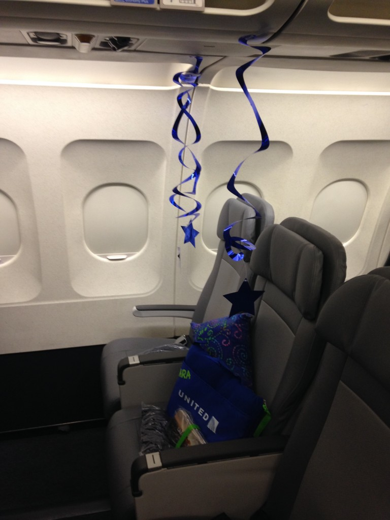 plane seat decorated with blue stars and gifts for make a wish kid heading to los angeles