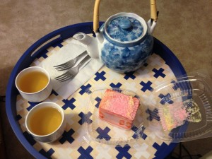 blue and white tea pot, tea cups with tea in them, and slice of strawberry cake on round wooden tray