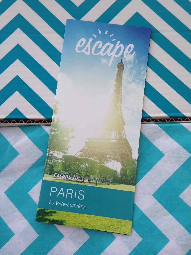 escape monthly august paris box info card against blue and white chevron background