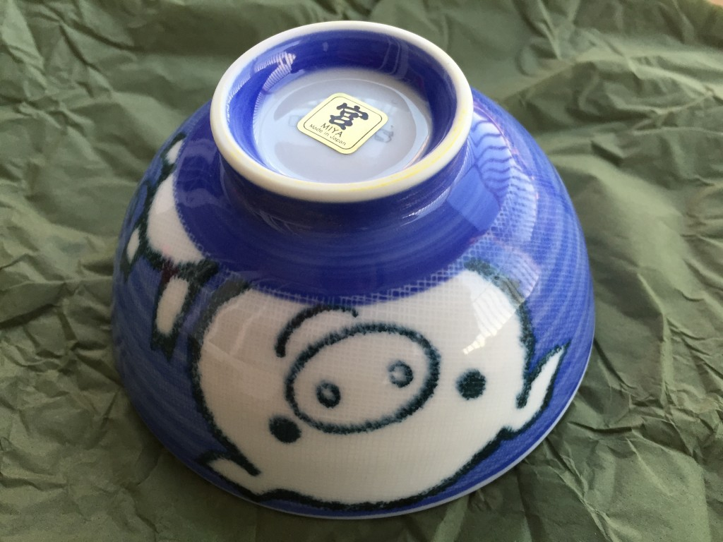 small blue bowl with cartoon pig design on side