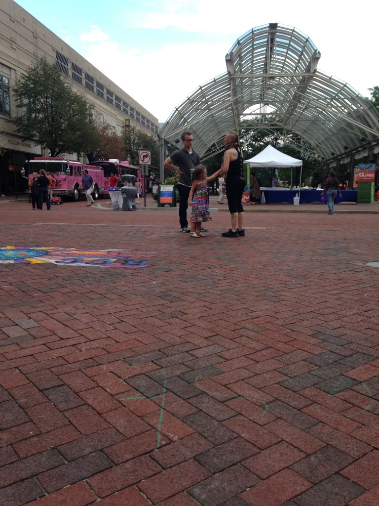 lady walking around reston town center with snake at chalkfest reston