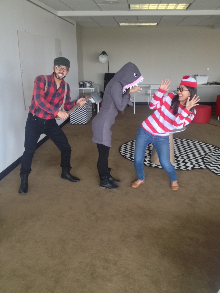 halloween trio dressed up as lumberjack with axe, shark, and waldo