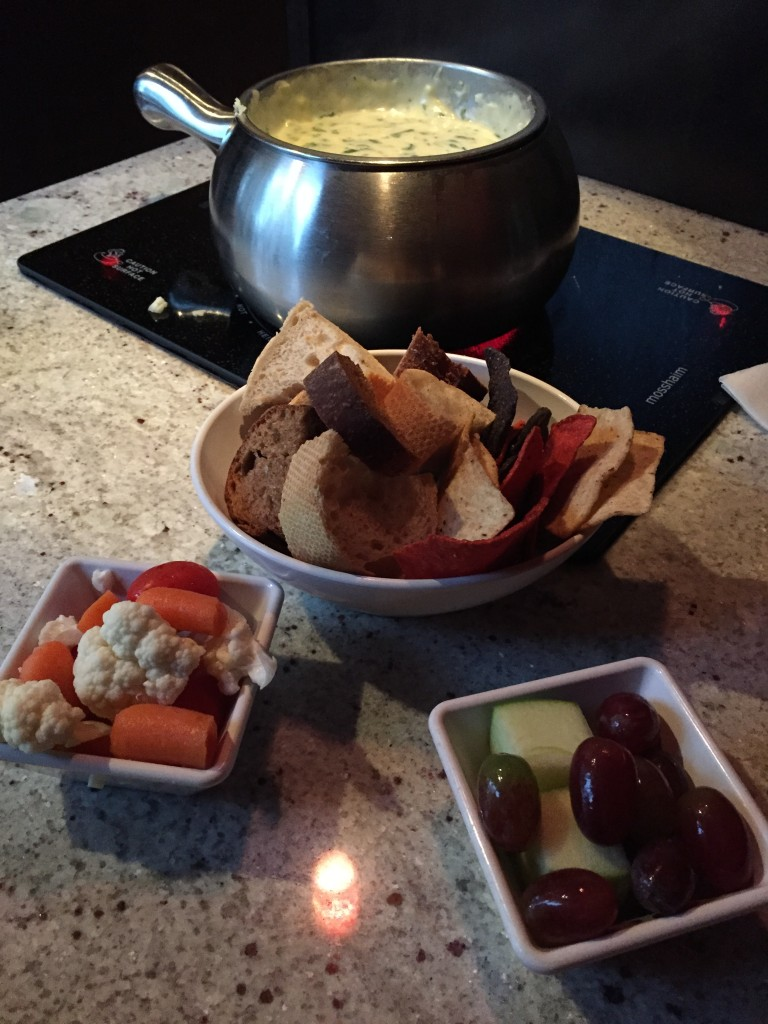 melting pot spinach artichoke cheese fondue with bread, chips, vegetables, and fruits for dipping