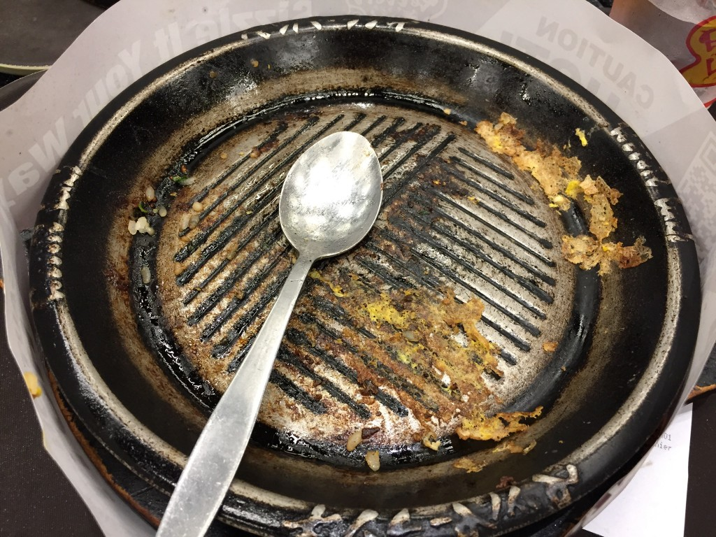 emptry pepper lunch skillet with spoon after meal has been eaten