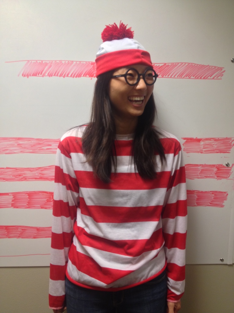laughing girl dressed up as waldo for halloween blending in with whiteboard with red stripes drawn on