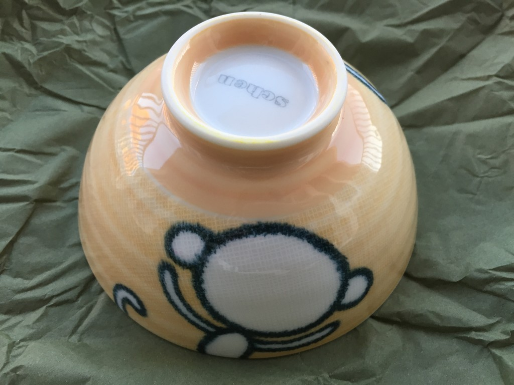 small yellow bowl with back of cartoon monkey outline on side