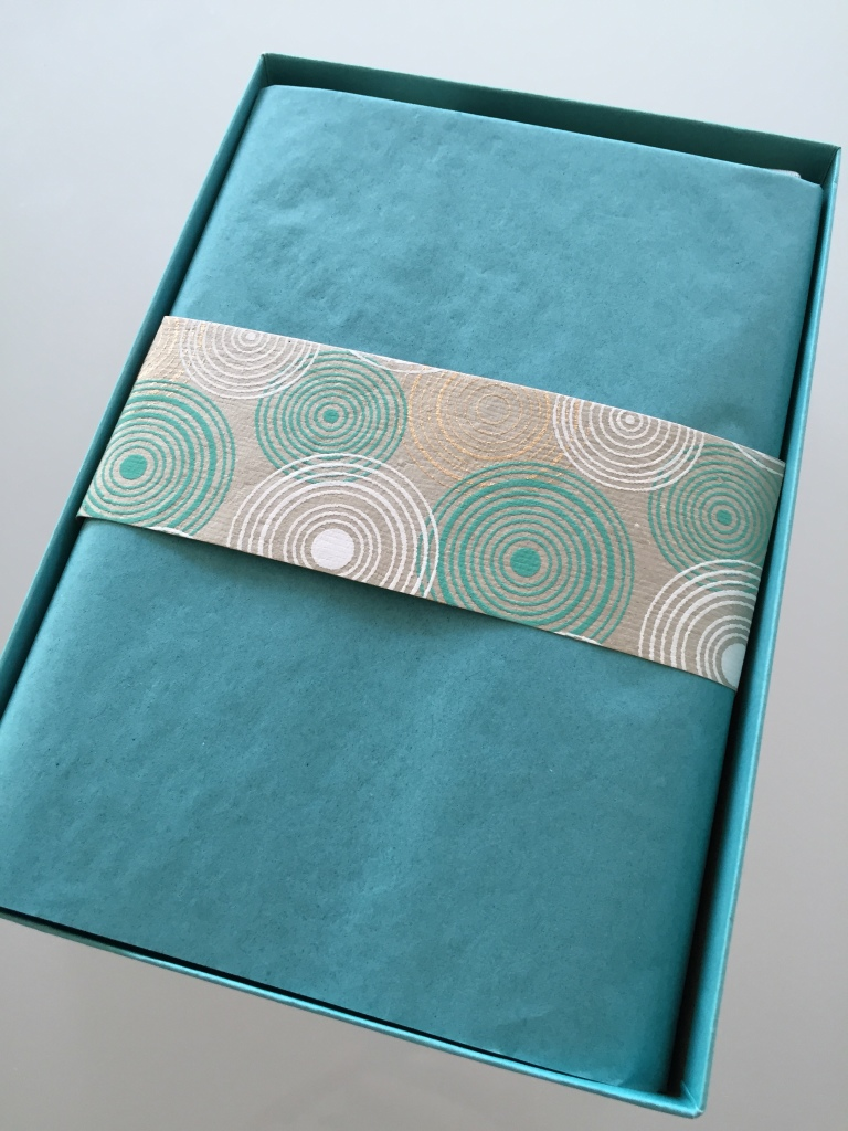 yuzen november-january 2014 winter box open with teal tissue paper and piece of yuzen paper