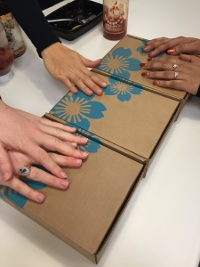 three people's hands each on a different yuzen box lined up