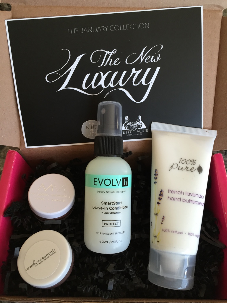 contents of petit vour january 2015 box with modern minerals eye shadow, rawskinceuticals cheek color, evolvh leave-in conditioner, 100% pure hand buttercream, and info card with the new luxury theme