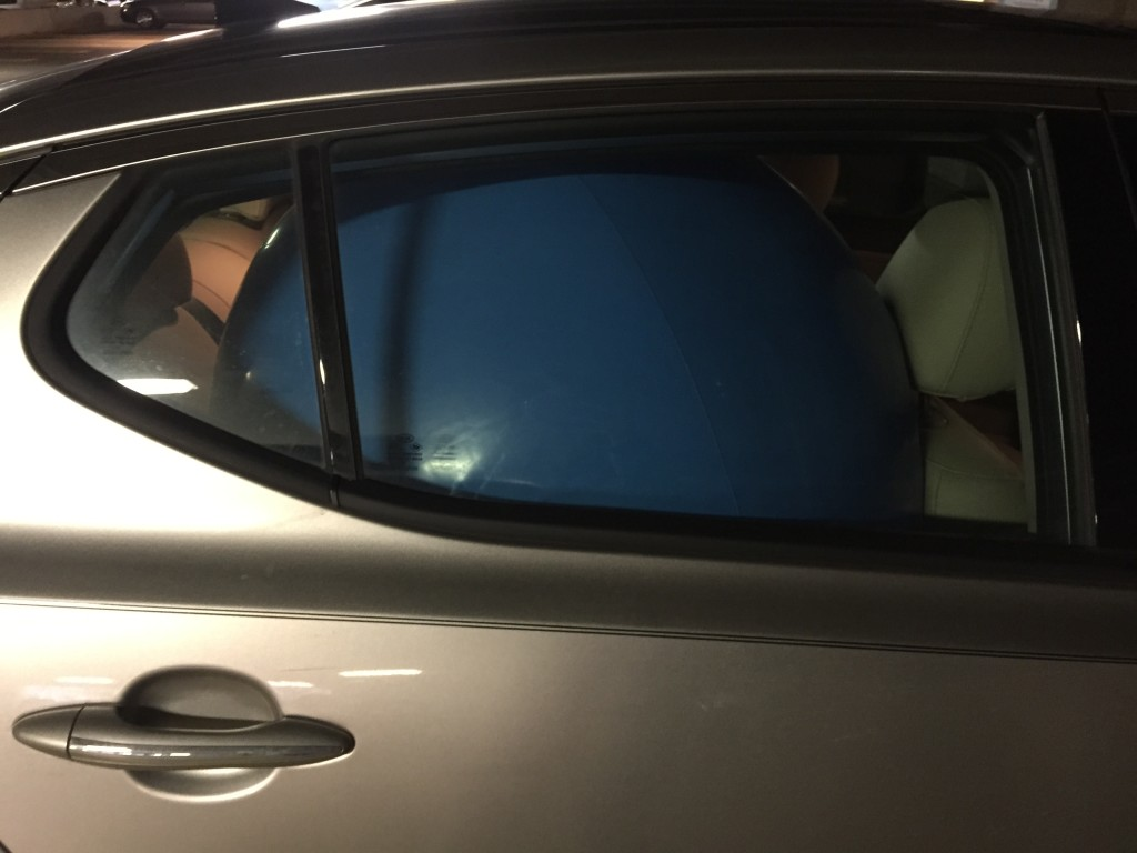 giant blue beach ball squished in back seat of car