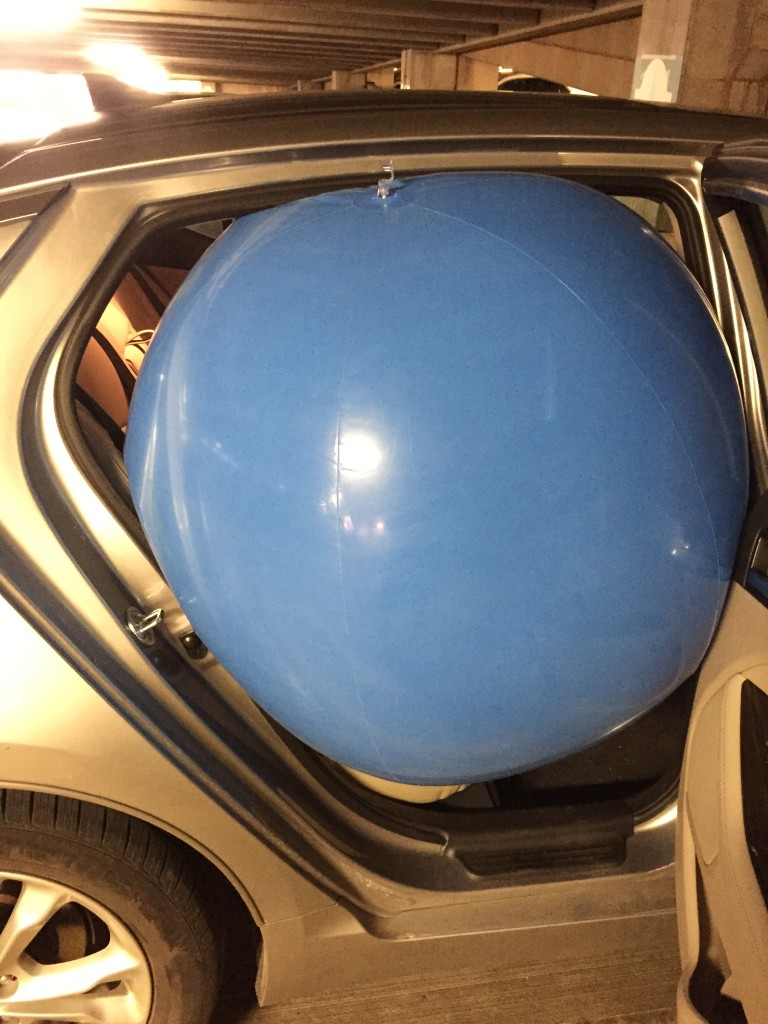giant blue beach ball squeezing into backseat of car